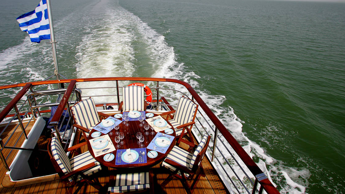 Sun deck aboard Callisto with set dining table at the stern.