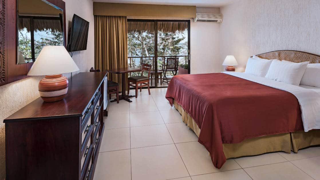 spacious room with a king sized bed and lamp on dresser next to a large glass door to the outside at Camino Real Tikal Hotel in Guatemala.