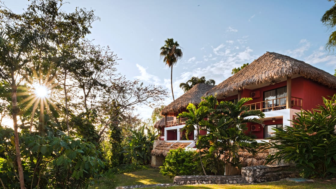 Exterior view of Camino Real Tikal Hotel in Guatemala with sun shining through the palm trees and clear blue skies