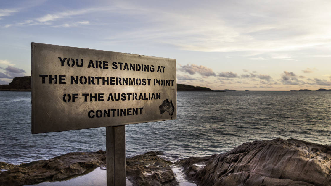 a sign stating 'you are standing at the northernmost point of the australian continent' sticks out of the sand with the ocean in the background at dusk