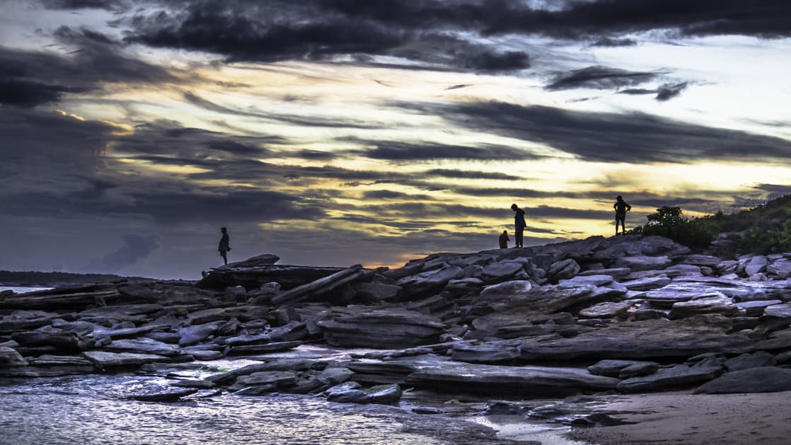 travelers explore a rocky shoreline at sunset on the Cape York and Arnhem Land small ship cruise