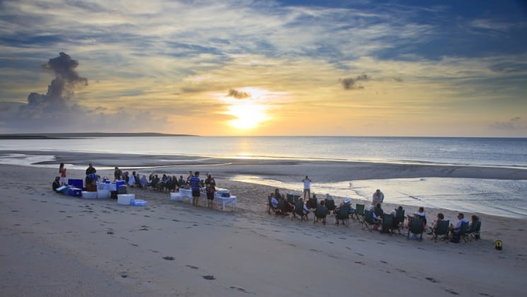 australia small ship cruise passengers relax on chairs at the beach during sunset with a calm ocean in front of them