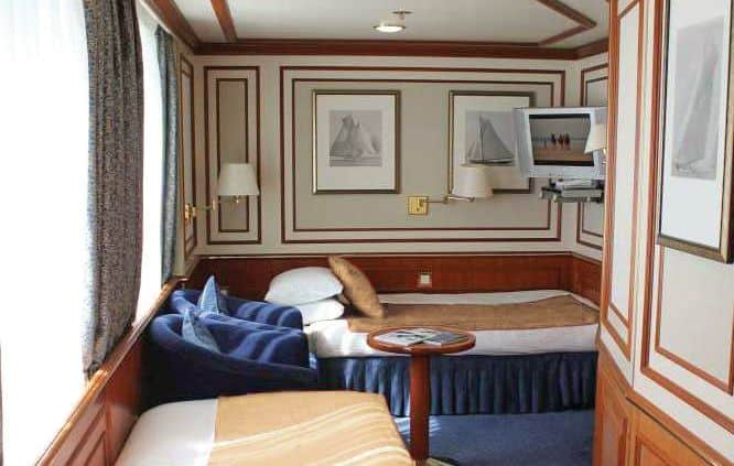 Cat 3S Suite with Window #512. This solo suite features two beds and two large windows, plus two armchairs and small table, reading lamps, a flat screen TV, and climate controls.