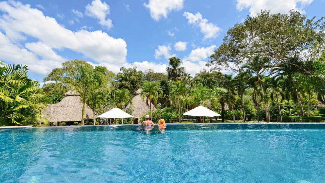 Panoramic view of cloudy blue skies and lush rainforest from the infinity pool at Chaa Creek Jungle Lodge in Belize