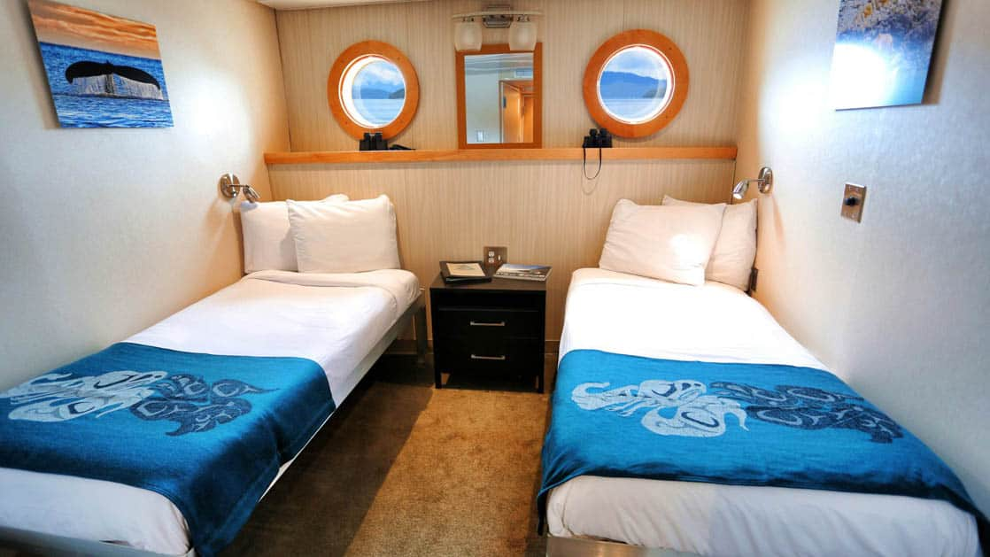 Category A stateroom aboard Chichagof Dream with two twin beds and two portholes.