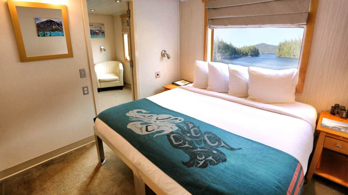 Main Deck Deluxe Suite aboard Chichagof Dream with large bed, window, and chair.