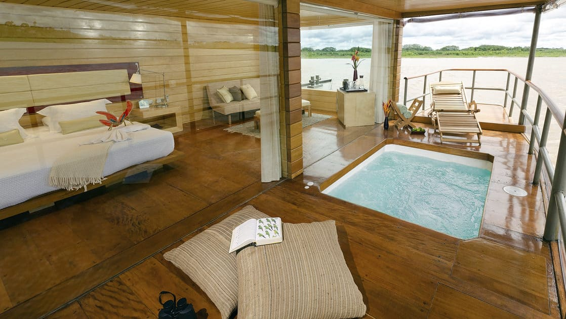 Deluxe Suite with bed, couch and private balcony with Jacuzzi aboard Delfin I on the Amazon River