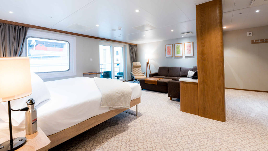 Bridge Deck Suite aboard Coral Adventurer with large bed, lounge area, and entry way.