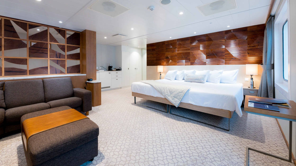 Bridge Deck Suite aboard Coral Geographer with large bed, sitting area, and entry way.