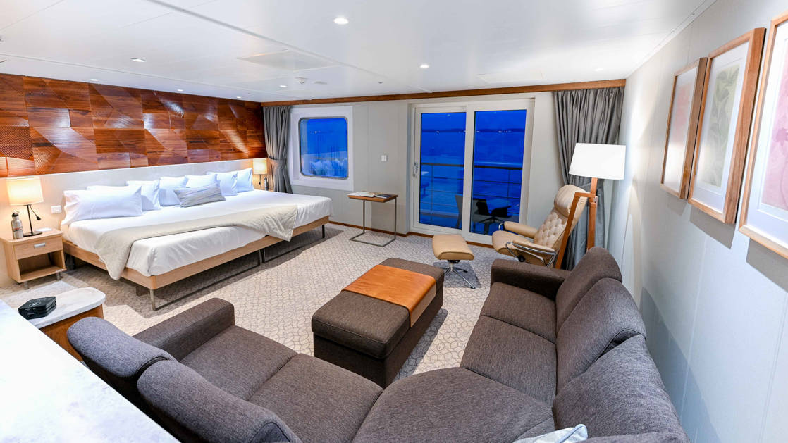Bridge Deck Suite aboard Coral Adventurer with large bed, verandah, and sectional couch.