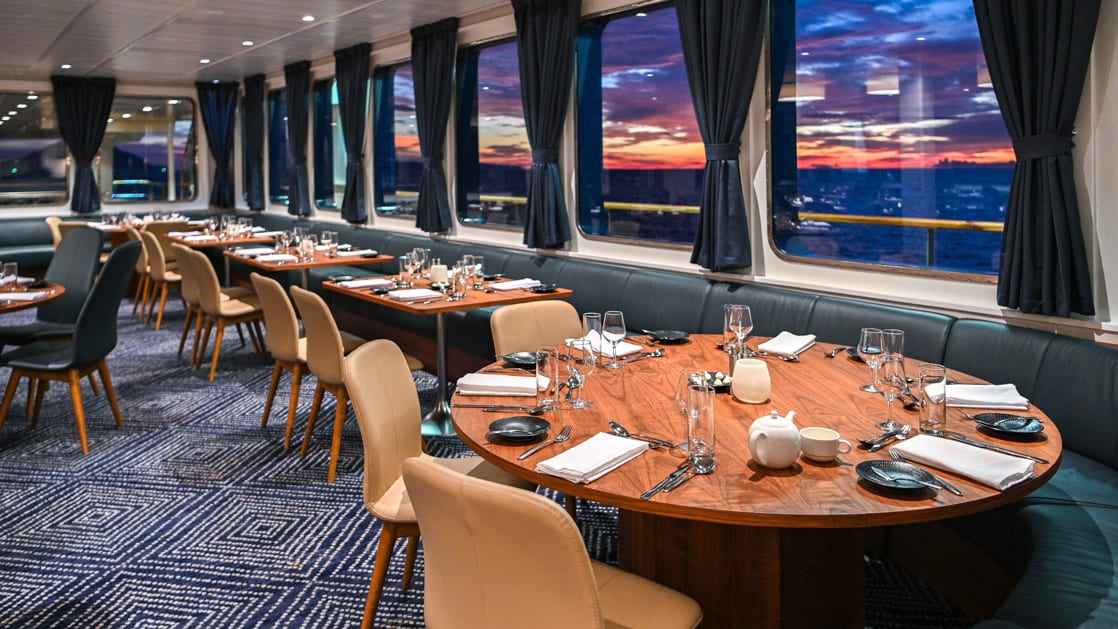 Empty dining room with set tables aboard Coral Adventurer.