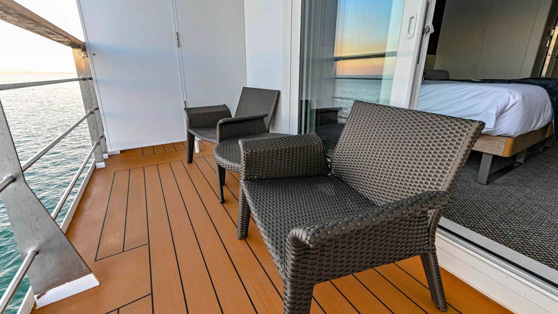 Explorer Deck Stateroom balcony aboard Coral Adventurer with two chairs and table.