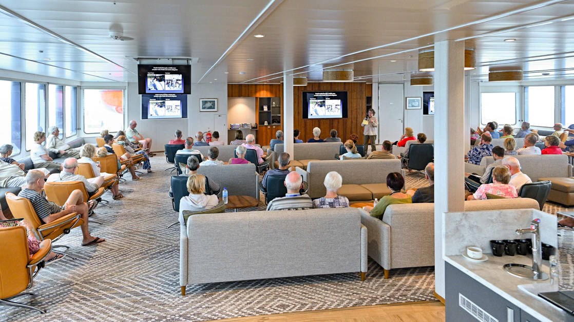 Lecture in the bridge deck lounge with sofas and tv screens aboard Coral Adventurer.