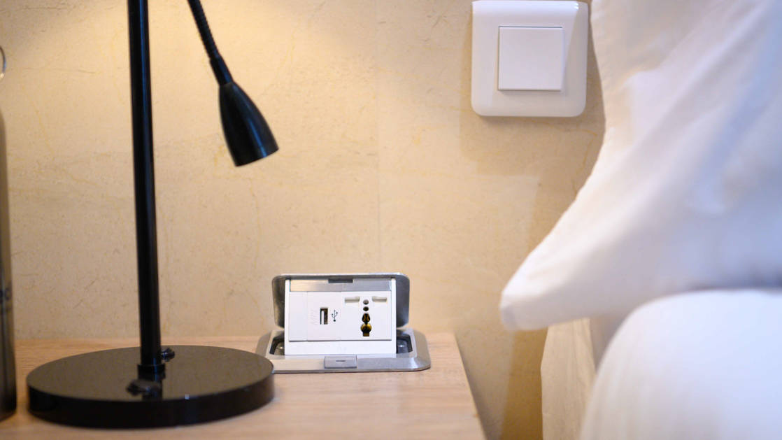 Universal power sockets and usb ports in lamp by bed in cabin.