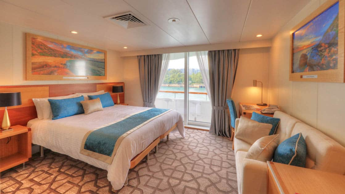 Bridge Deck Balcony stateroom aboard Coral Discoverer with large bed, couch, and balcony.