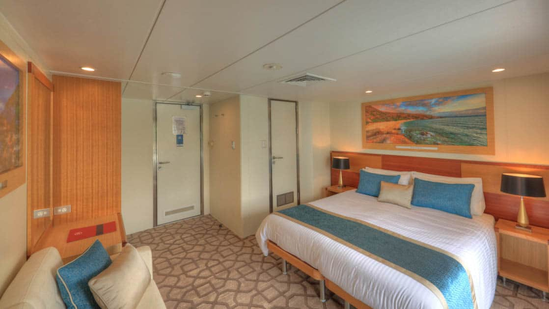 Bridge Deck Balcony stateroom aboard Coral Discoverer with large bed, couch, wardrobe, and doorway.