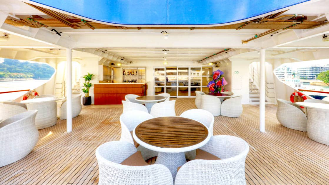 Bridge deck outdoor bar with tables and chairs aboard Coral Adventurer.