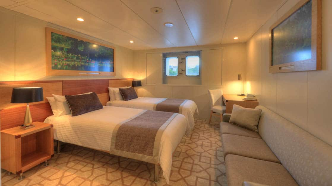 Main Deck stateroom aboard Coral Discoverer with two twin beds, couch, and window.