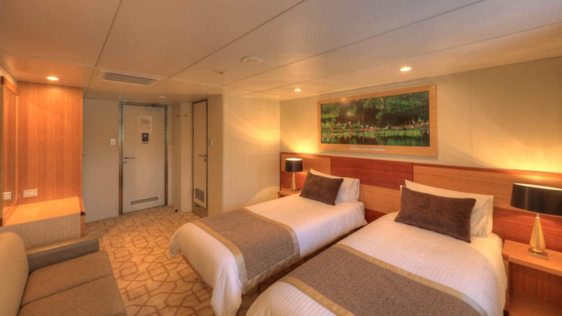 Main Deck stateroom aboard Coral Discoverer with two twin beds, couch, and doorway..