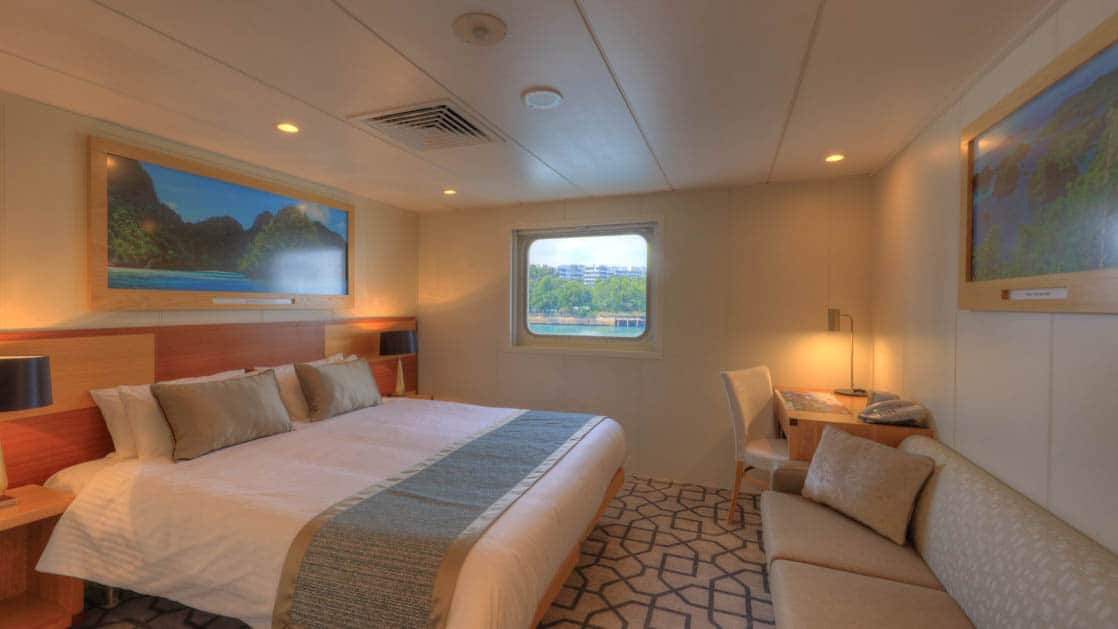 Promenade Deck stateroom aboard Coral Discoverer with bed, couch, and window.