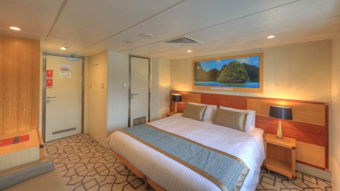 Promenade Deck stateroom aboard Coral Discoverer with bed, couch, and doorway.