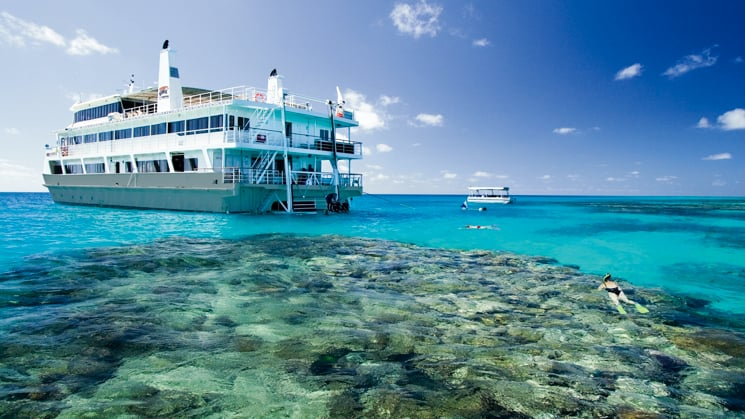 Port side of Coral Expeditions II with snorkelers exploring the Great Barrier Reef