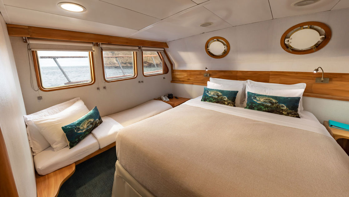Double bed with tan bedding & decorative pillows, flanked by bedside bench set up for sleeping, aboard Corals Galapagos yachts.