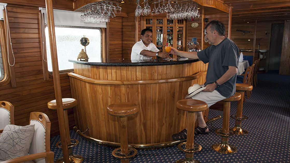 Bartender serving man tropical drink at bar aboard Coral I & Coral II yachts in the Galapagos Islands