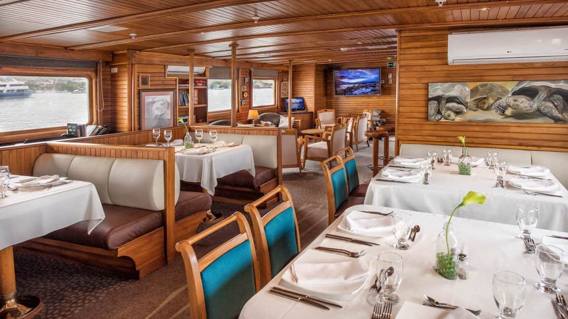 Set tables and booths with large windows in the dining room aboard Coral II yacht in the Galapagos Islands