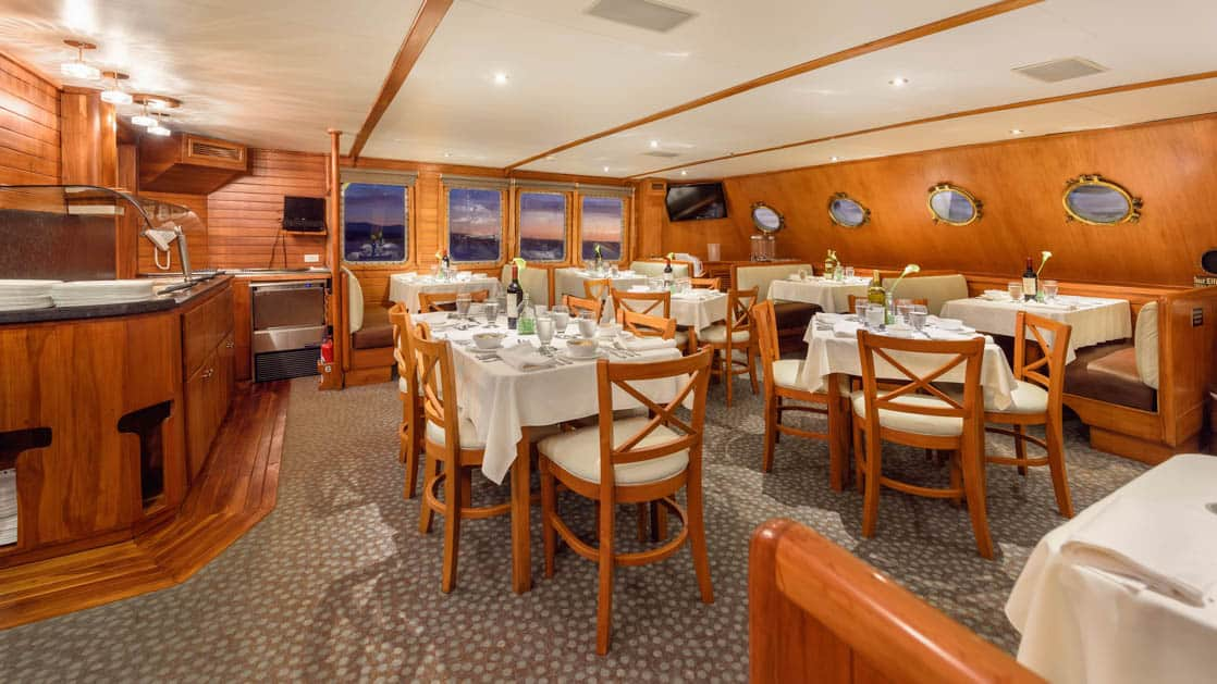 The Coral I Dining Room with set tables, booths and large windows in the Galapagos Islands