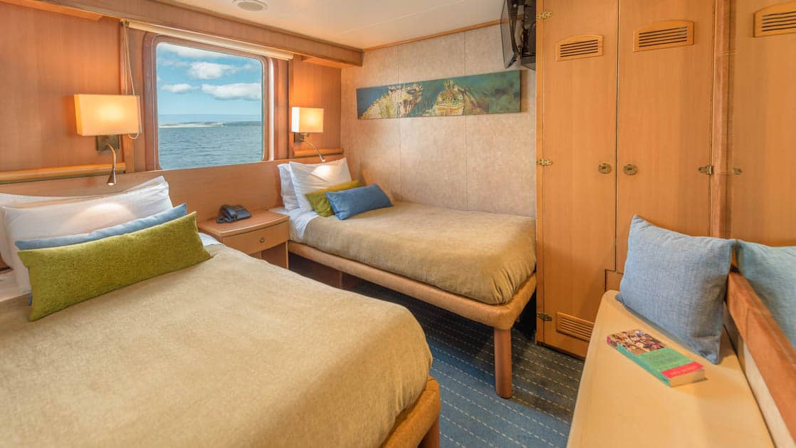 Junior Cabin with two beds, bench, bureau, TV and picture window aboard Coral I & Coral II yachts in the Galapagos Islands