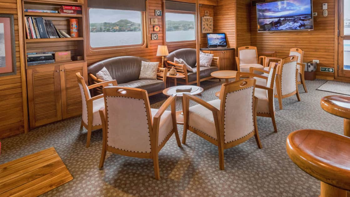 Lounge area with couches, chairs, tables, bookcases, computer and large TV aboard Coral I & Coral II yachts in the Galapagos Islands
