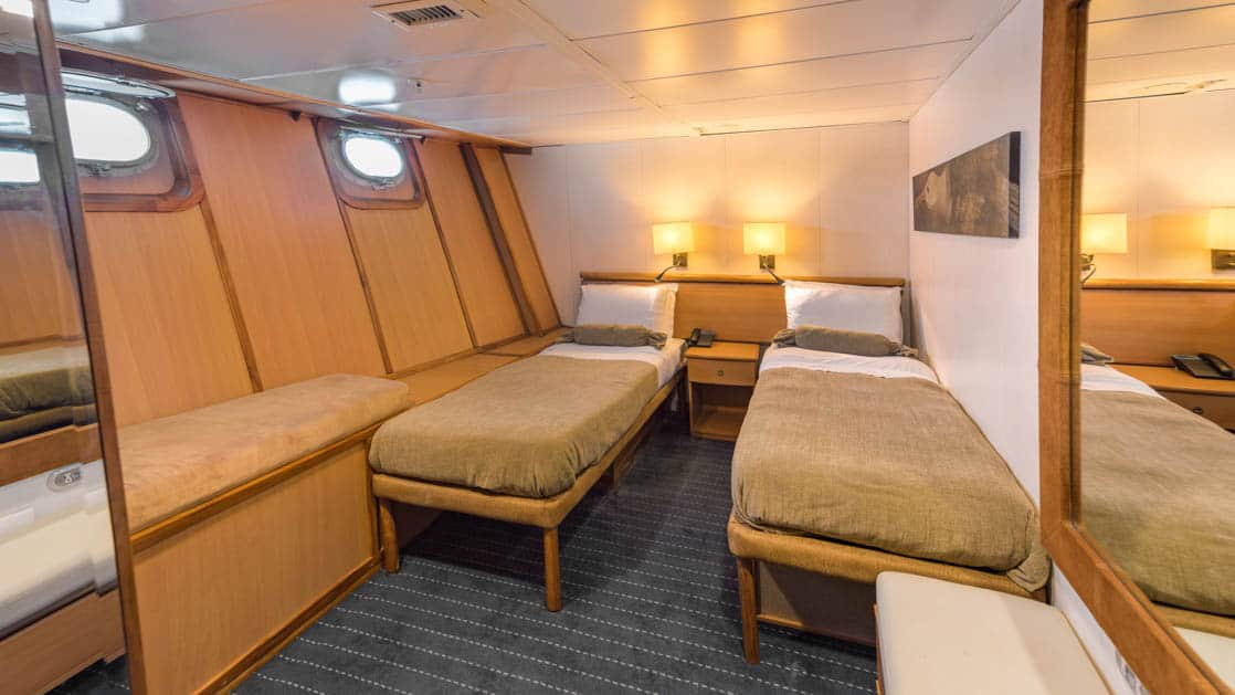 Standard Plus Cabin with two beds, bench, bedside table and two portholes aboard Coral I & Coral II yachts in the Galapagos Islands