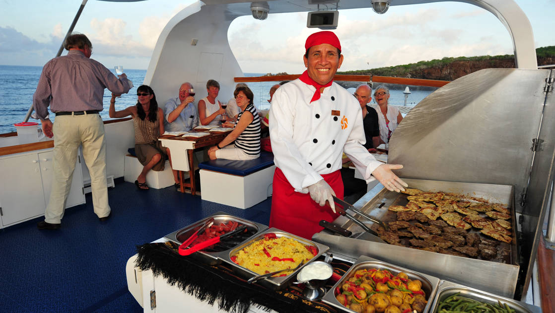 Chef preparing food on large grill on deck of Coral I & Coral II yachts in the Galapagos Islands