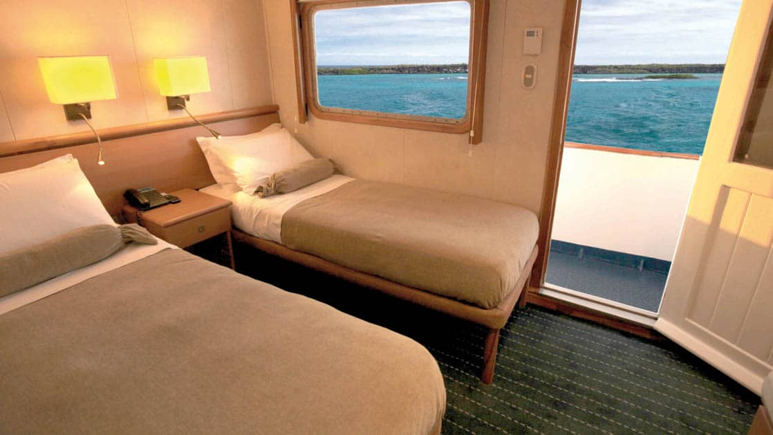 Junior Cabin with two beds, bedside table, large window and balcony aboard Coral I & Coral II yachts in the Galapagos Islands