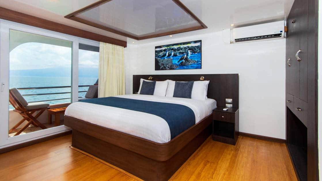 double bed with large windows and balcony with lounge chair outside aboard the Cormorant in the Galapagos