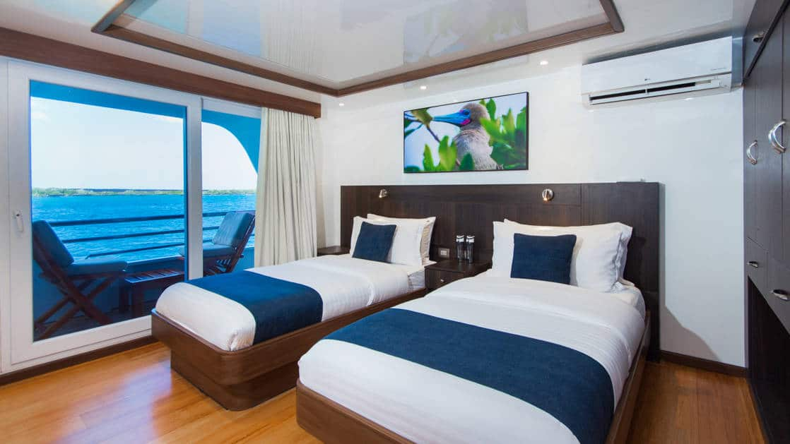 Two twin beds with large sliding glass door to balcony with lounge chair aboard the Cormorant in the Galapagos