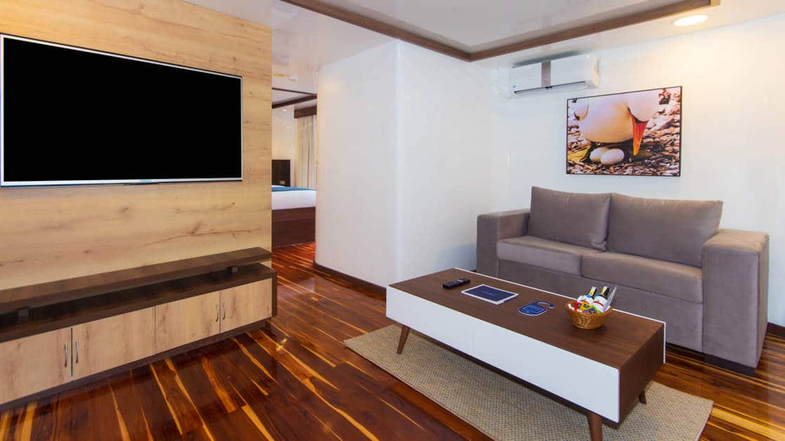 large living suite with TV and couch and coffee table aboard the Cormorant in the Galapagos