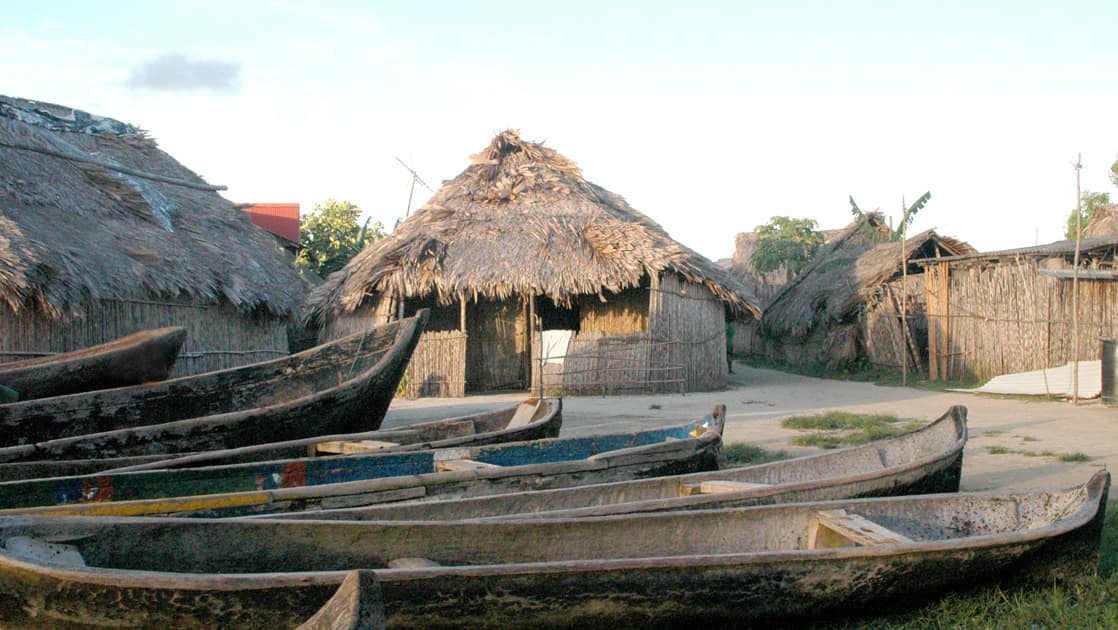 native canoe boats sitting in front of thatched buildings on a sunny day in panama