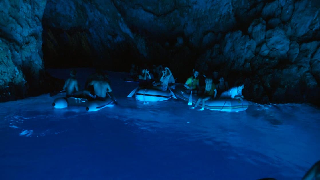 travelers in small boats lining the walls of the blue cave bisevo croatia on the dalmatian coast cruise