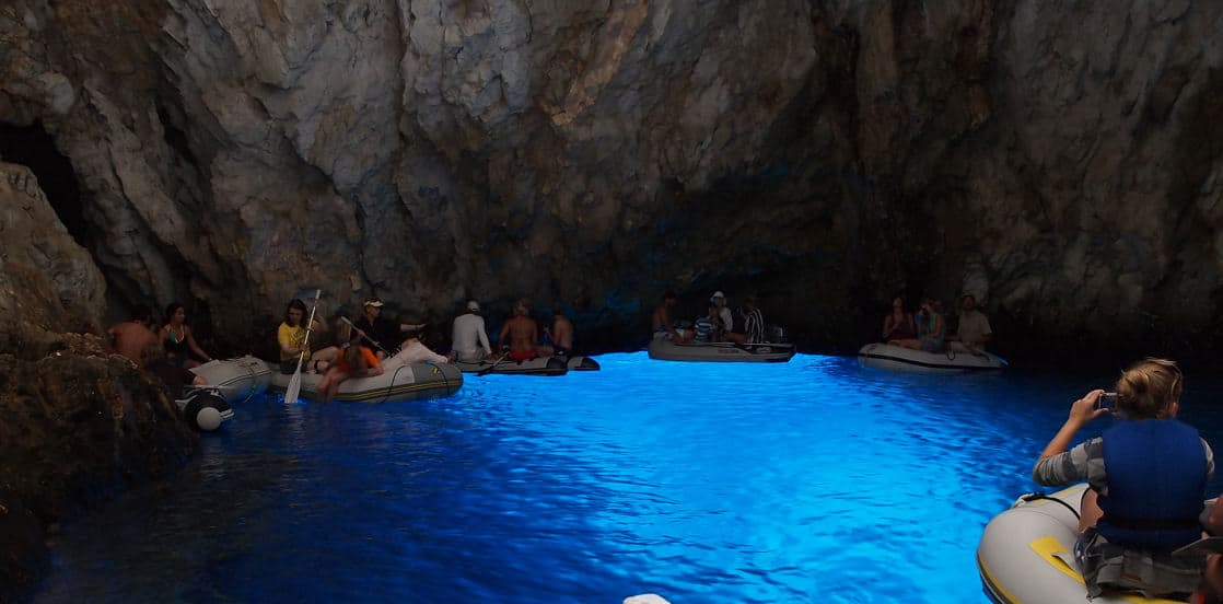 the blue cave on the dalmatian coast croatia with adventure travelers in small boats floating along the interior walls