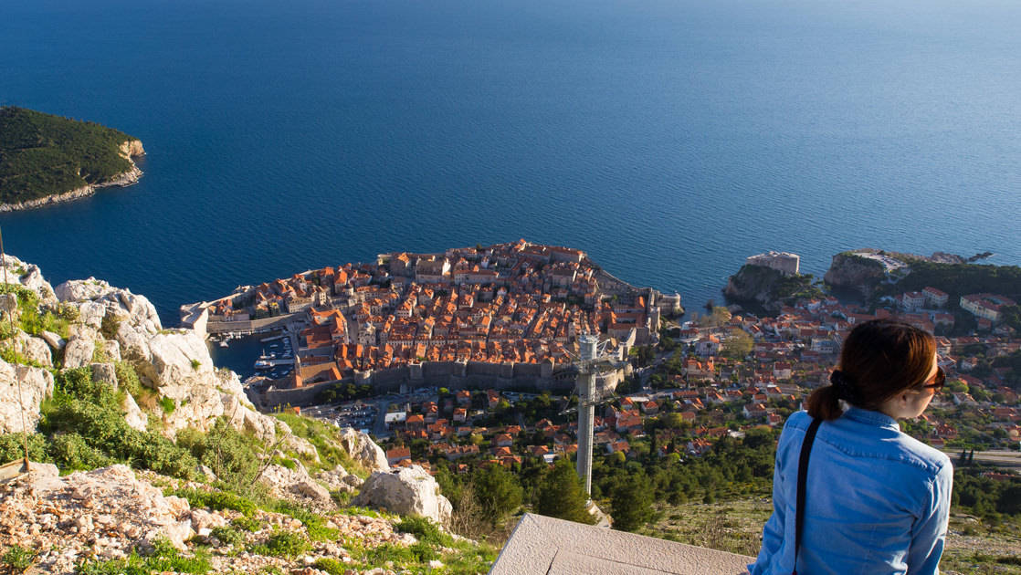 a woman traveler looking down at dubrovnik and the mediterranean on a sunny day on the dalmatian coast