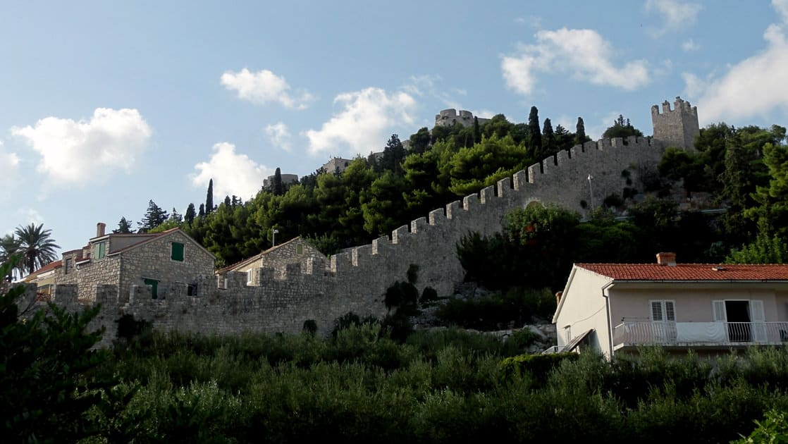 a long castle wall in hvar croatia on a sunny day, lined on either side by thick green trees seen on the dalmatian coast cruise