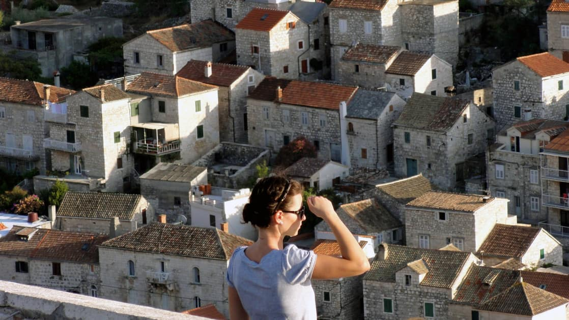 a woman shading her eyes looking down on the buildings of hvar croatia on a sunny day