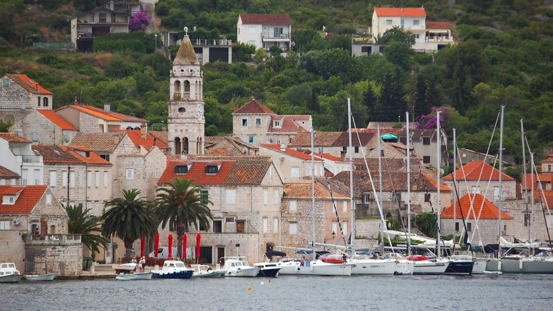 a town on the water with yachts and small ships in the harbor with green trees behind it seen on the dalmatian coast cruise
