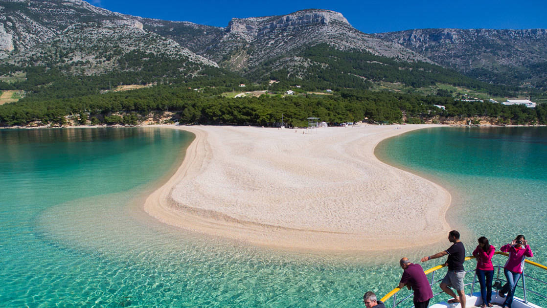 zlatni rat beach croatia on a sunny day with clear blue water of the mediterranean around it and mountains behind it