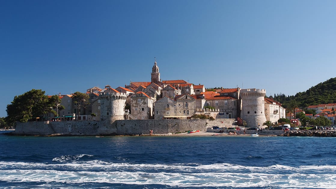 korcula croatia passed on the dalmatian coast cruise seen by a small ship with the blue water of the mediterranean in the foreground