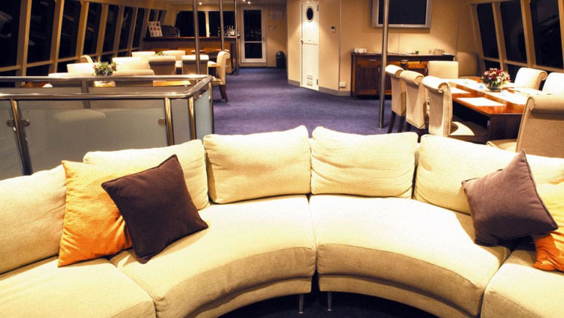 a couch with tables and chairs in the background aboard panama discovery catamaran