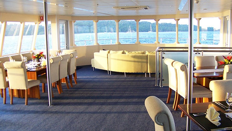 room with tables, chairs and a couch, and a row of windows at the end aboard the panama discovery catamaran