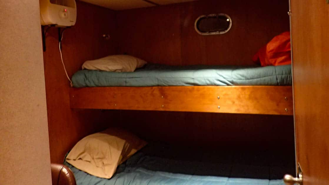 Dream Catcher stateroom with twin berth bunk beds and small porthole.